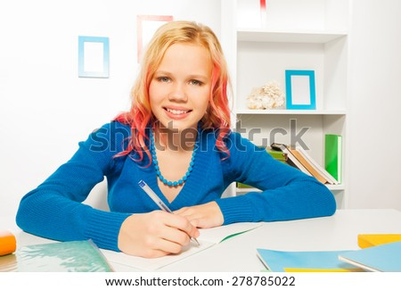 Happy girl smile, write in textbook doing homework - stock photo