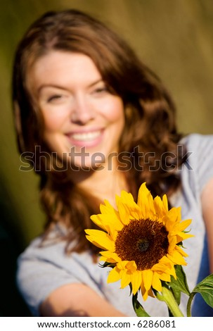 happy girl smiling and offering a sunflower - stock photo