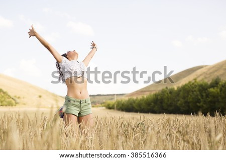 Happy girl smiling in field - stock photo