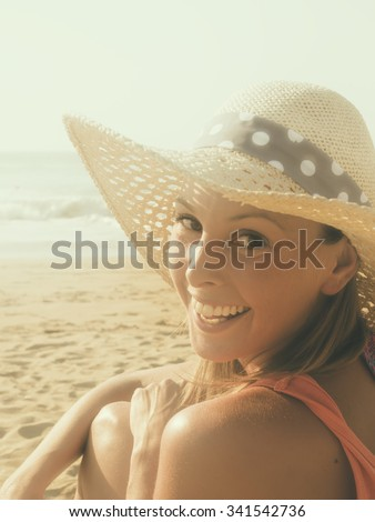 happy girl smiling profile photo in the beach  wearing a  hat with the sea and horizon in the background, portrait - stock photo