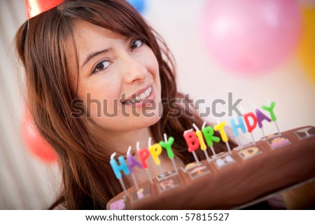 Happy girl smiling with a birthday cake in front of her face - stock photo