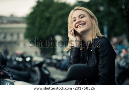 Happy girl speaking on the phone while sitting on her scooter - stock photo