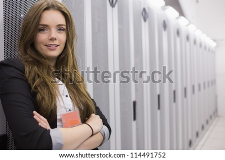 Happy girl standing in data storage facility with arms folded - stock photo