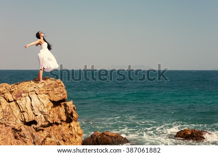 Happy girl standing outdoor on edge cliff sea shore. Happiness and freedom enjoy - stock photo