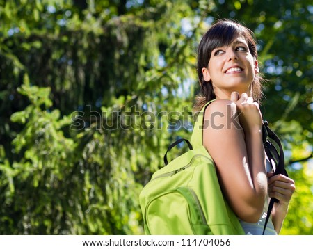 Happy girl student on summer / spring park with backpack. College girl with school bag smiling happy. Young brunette caucasian university student outdoor. - stock photo