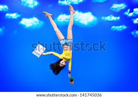 Happy girl student standing upside down with a book over blue sky. - stock photo