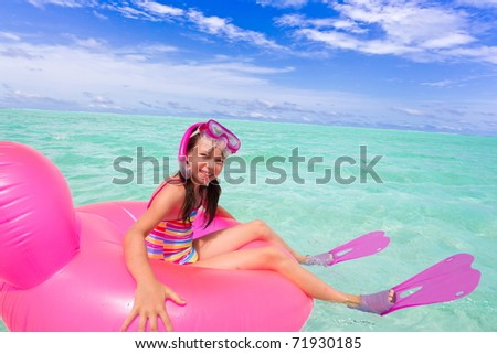 Happy girl swimming in the tropical ocean waters of the Maldive Islands. - stock photo