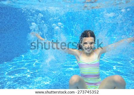 Happy girl swims in pool underwater, active kid swimming, playing and having fun, children water sport  - stock photo
