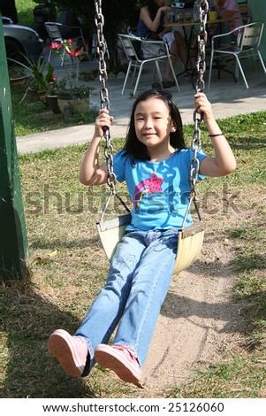 Happy girl swinging at the playground in the park on sunny day - stock photo