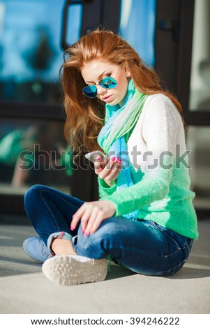 Happy girl texting on a smart phone. A portrait of a smiling beautiful woman texting with her phone. Beautiful casual woman texting on her cell phone - stock photo