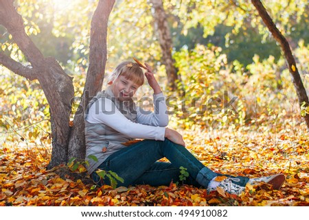 Happy girl under the tree in autumn