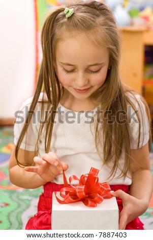Happy girl unpacking the birthday present - stock photo