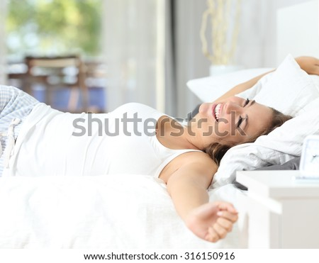 Happy girl waking up stretching arms on the bed in the morning - stock photo