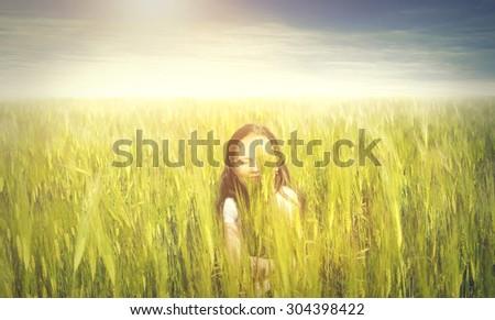 Happy girl walking in a field - stock photo