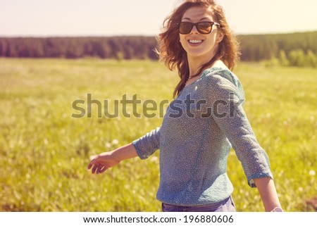 Happy girl walking on summer field. - stock photo