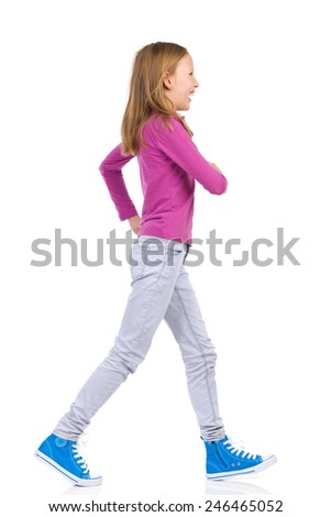 Happy girl walking. Walking teen girl, side view. Full length studio shot isolated on white.