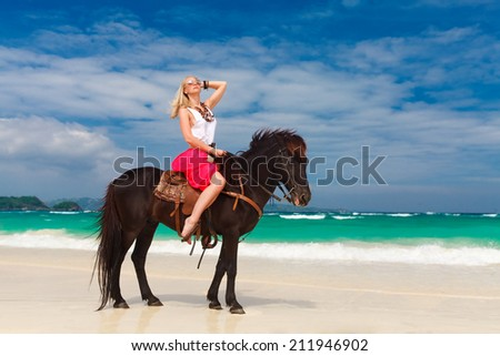 happy girl walking with horse on a tropical beach