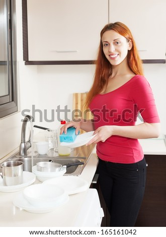 Happy girl washing plates in home kitchen - stock photo