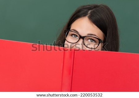 Happy girl wearing glasses sitting in class reading a large textbook peering over the top with smiling eyes - stock photo