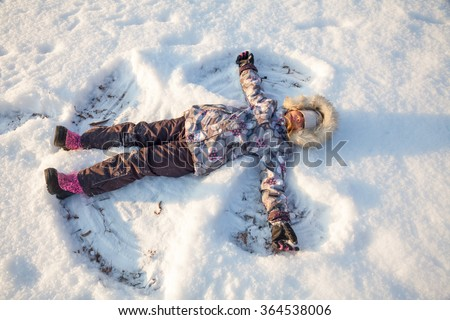 Happy girl wearing warm winter clothing having fun laying in a fresh snow making snow angels - stock photo