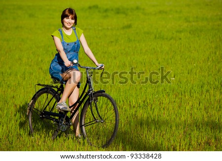 Happy girl with a bicycle in a green meadow - stock photo