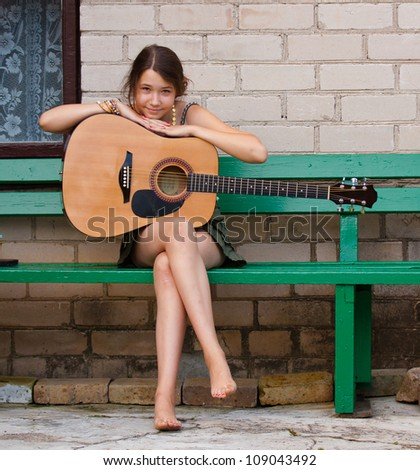 Happy girl with a guitar, smiling and looking at the camera - stock photo