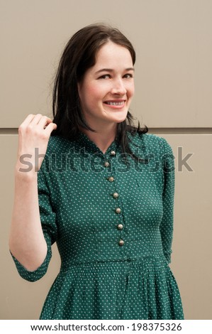 Happy girl with a natural look smiling and wearing a green dress with white dots - stock photo