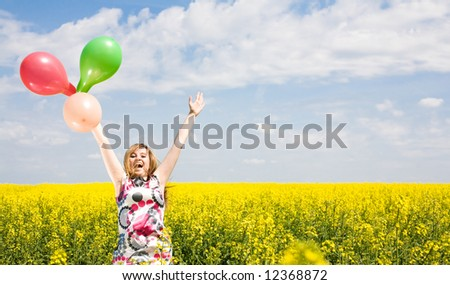 Happy girl with balloons on the rapeseed field.