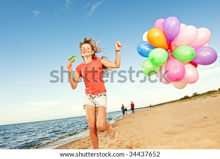 Happy girl with balloons running on the beach