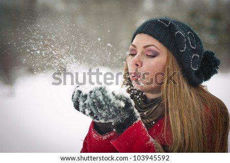 Happy girl with cap and gloves playing with snow in the winter landscape - stock photo