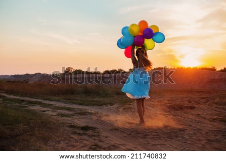 Happy girl with colorful balloons at sunset - stock photo