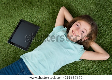 Happy Girl With Digital Tablet And Mobile Phone Lying On Green Lawn