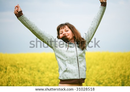 Happy girl with fluttering hair in flower field