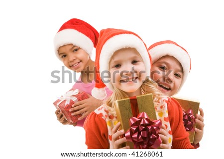 Happy girl with giftbox looking at camera with her friends at background