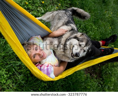 Happy girl with her dog resting in  hammock - stock photo