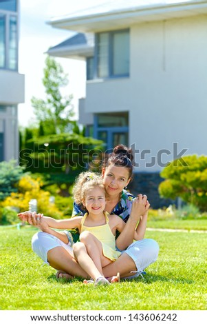 Happy girl with her mother sitting on the lawn in front new cottage. Vertical view - stock photo