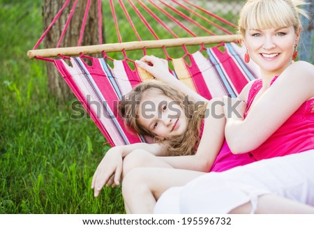 Happy girl with mother  in colorful hammock - stock photo