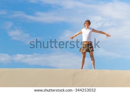 Happy girl with open arms standing on the sand dune. Turkey, Patara. - stock photo