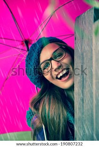 happy girl with pink umbrella laughing - stock photo