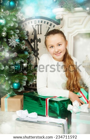 Happy girl with presents while Christmas time - stock photo