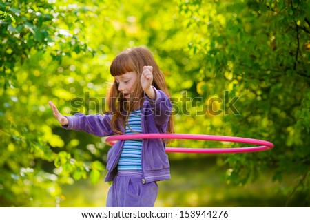 happy girl with red hair with a hula-hoops - stock photo