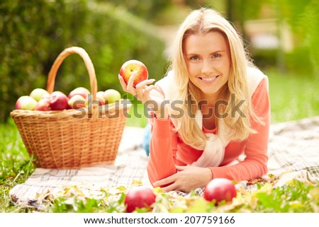 Happy girl with ripe red apple looking at camera while lying on grass
