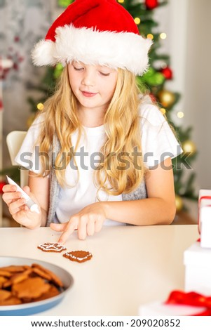 Happy Girl with Santa Hat decorating Christmas gingerbread cookies with christmas tree at background - stock photo