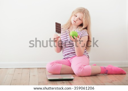 happy girl  with scales, fruits and chocolate - stock photo