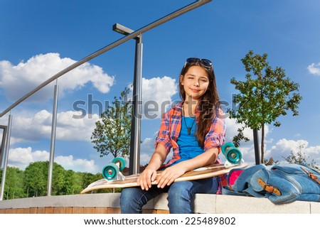 Happy girl with skateboard sitting alone outside - stock photo