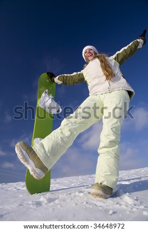 Happy girl with snowboard at sunny day at winter