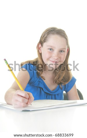 Happy girl working on school assignment - stock photo