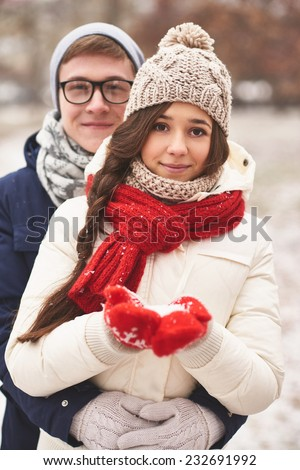Happy girlfriend in casual winterwear and her boyfriend embracing her behind looking at camera outdoors  - stock photo