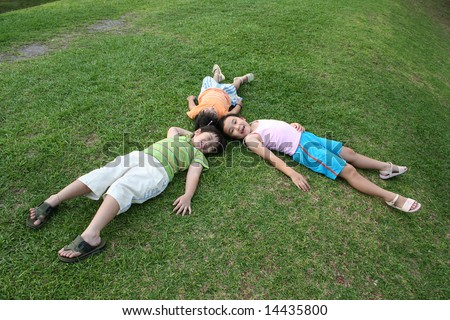 Happy girls and boy lying on the grass - stock photo