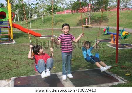 Happy girls and boy playing swing in the park